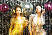 Two beautiful sexy disco women in gold and silver catsuits danci — Stock Photo