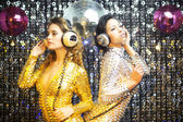 Two beautiful sexy disco women in gold and silver catsuits danci — Stockfoto