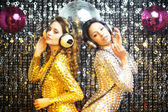 Two beautiful sexy disco women in gold and silver catsuits danci — Stock fotografie