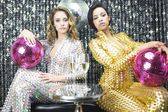 Two beautiful sexy disco women in gold and silver catsuits danci — Foto de Stock
