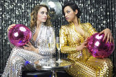 Two beautiful sexy disco women in gold and silver catsuits danci — ストック写真
