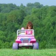 Stock Video: Girl Driving Toy Jeep