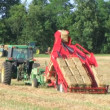 Stock Video: Farmer Square Baling Hay