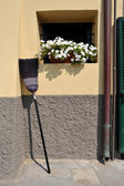 Broom propped against the wall — Stock Photo