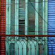 Green wood venetian blind and a red blue wall - Stock Photo