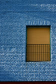Old yellow window in light blue wall — Stock Photo
