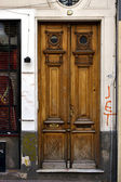 Brown wood old door and a grate — Stock Photo