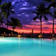 Stock Photo: Swimming pool sunset parasol in nosy be