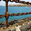 Rusty chain  water  boat  and sr in lanzarote spain — Stock fotografie