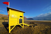 Water lifeguard chair cabin red flag in spain lanzarote rock s — Stock Photo