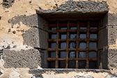 Brown distorted castle window in a broke wall arrecife — Stock Photo