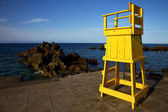 Yellow lifeguard chair cabin in spain rock stone sky cloud b — Stock Photo