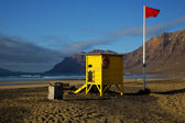Lifeguard chair red flag in spain coastline and summer — Stock Photo