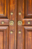 brown knocker in a   closed wood door crenna gallarate varese   — Stock Photo