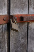 Old bar lock hanging on wooden doors — Stock Photo