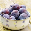 Plums on shabby wooden table — Stock Photo