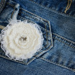 Ivory flower brooch on denim background — Stock Photo