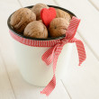 Walnuts in white bucket bounded up in red ribbon and bow — Stock Photo #15978759