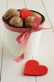 Walnuts in white cup and two red hearts — Stok fotoğraf