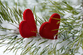 Two red hearts in pine needles covered with snow — Stock Photo