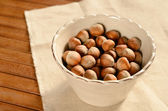 Unshelled hazelnuts in cute bowl on wooden table — Stock Photo
