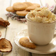 Cup of whipped cream coffee and apple cookies on wooden table — Stock Photo #21600115