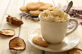 Cup of whipped cream coffee and apple cookies on wooden table — Stock Photo