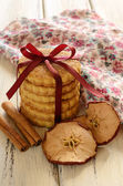 Pile of apple cookies tied up with ribbon and bow on wooden tabl — Stock Photo