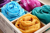Set of colorful scarves in wooden box — Stock Photo