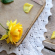 Stock Photo: Yellow rose laying upon vintage book on lace doily