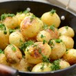 Whole fried potato in old wok — Stock Photo