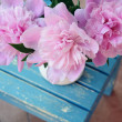 Bunch of peony on shabby blue chair — Stock Photo