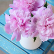 Bunch of peony on shabby blue chair — Stock Photo #25914445