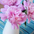 Bunch of peony on shabby blue chair — Stock Photo #25914447