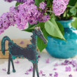 Decoration with horse statuette and lilac — Stock Photo #26464693