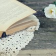 Open book on lace doily on rusted garden table — Stock Photo