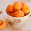 Ripe apricots in a tea cup — Stock Photo