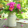 Stock Photo: Wild rose bouquet in old milk churn