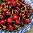Sweet cherry in blue oriental bowl — Stock Photo