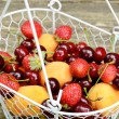 Mix of summer fruits and berries in wire basket — Stock Photo