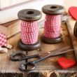 Decoration with wooden spools and red ribbons — Stock Photo #30539851