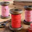 Decoration with wooden spools and red ribbons — Stock Photo