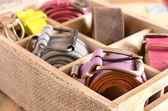 Set of stylish belts in wooden crate — Stock Photo