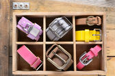 Set of stylish belts in wooden crate on rusted wooden boards — Stock Photo