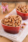 Caramelized almond with cinnamon in shart shaped red bowls — Stock Photo