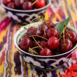 Ripe cherry in oriental bowls on pattern ethnic fabric — Stock Photo
