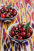 Ripe cherry in oriental bowls on bright ethnic tablecloth — Stock Photo