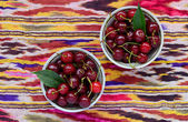 Bowls with ripe cherry over bright oriental tablecloth — Stock Photo