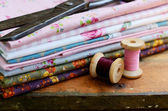 Set of different fabrics, wooden thread spools and tailor scisso — Stock Photo