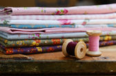 Set of different fabrics and wooden thread spools — Stock Photo